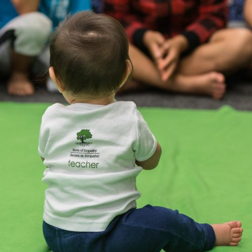 baby with Roots of Empathy t shirt sitting
