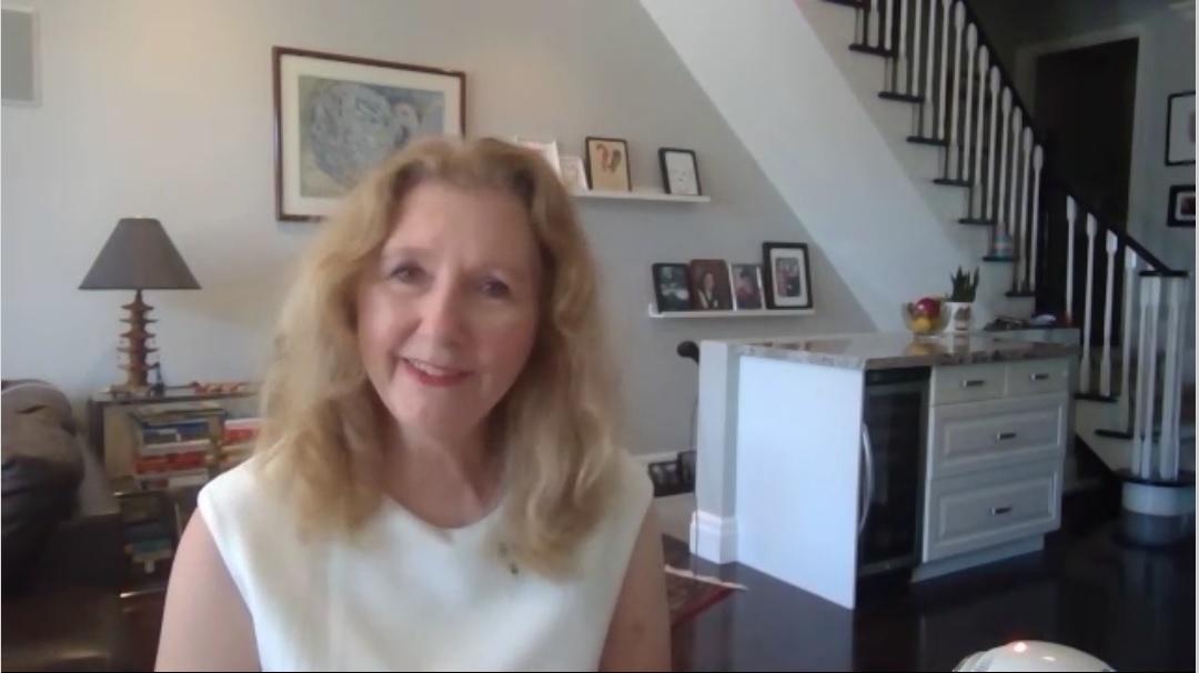 Mary Gordon wearing white sleeveless blouse speaking to camera